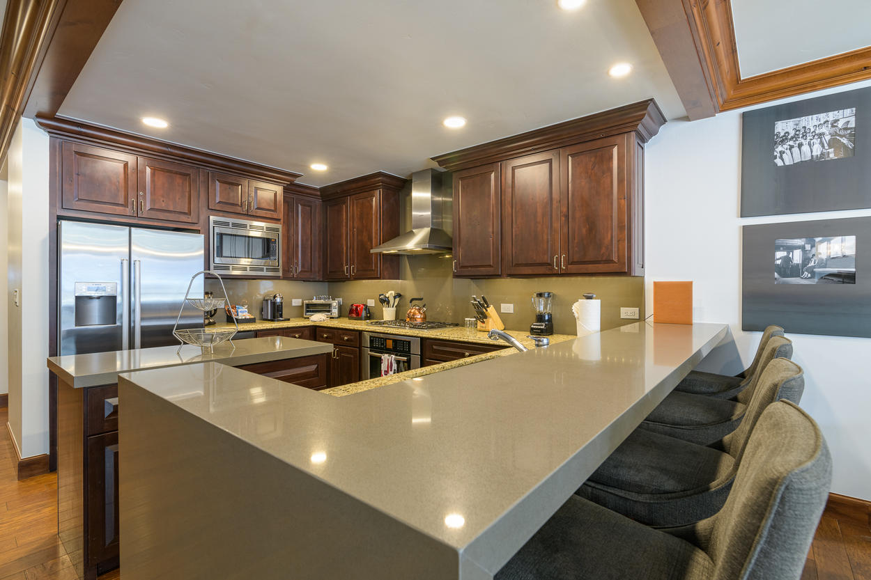 The kitchen has a two-tiered counter between the breakfast bar and kitchen counter.