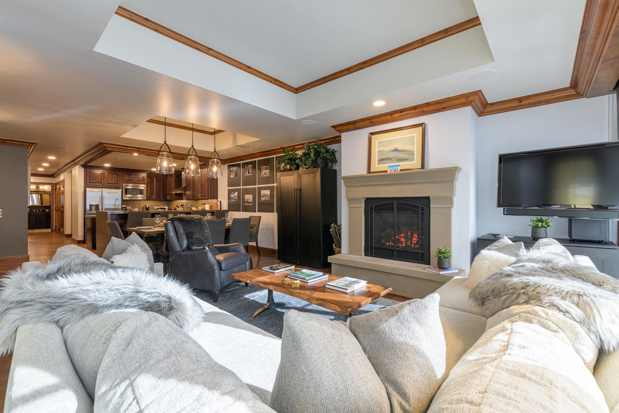 The sectional couch in the living area sits in front a large flatscreen TV and the gas fireplace.