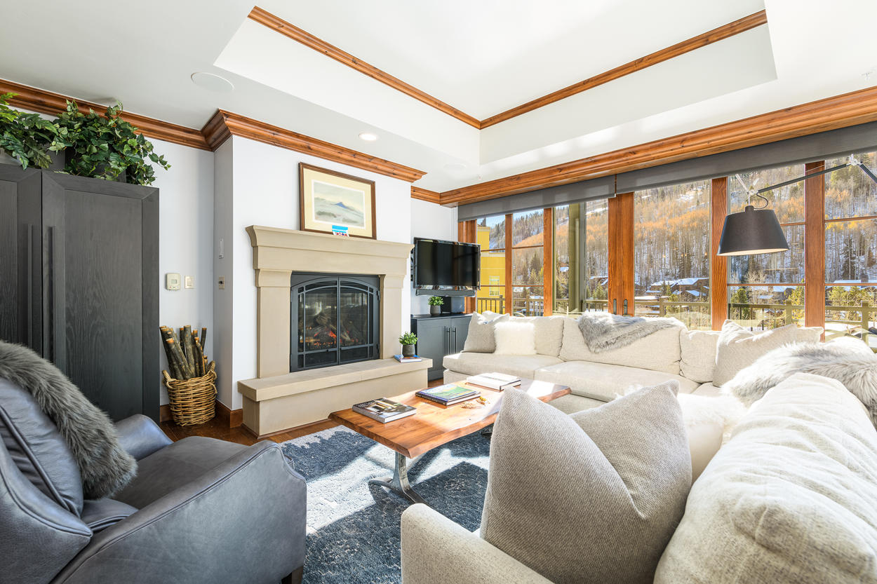 The living room features a sprawling wraparound couch and plush leather chair so your whole group can relax together.