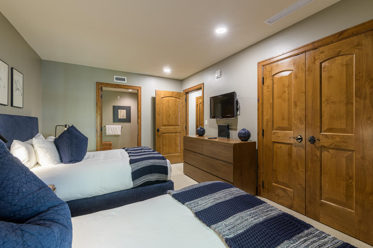 In front of the queen beds there's a mounted TV and access to the ensuite bathroom.