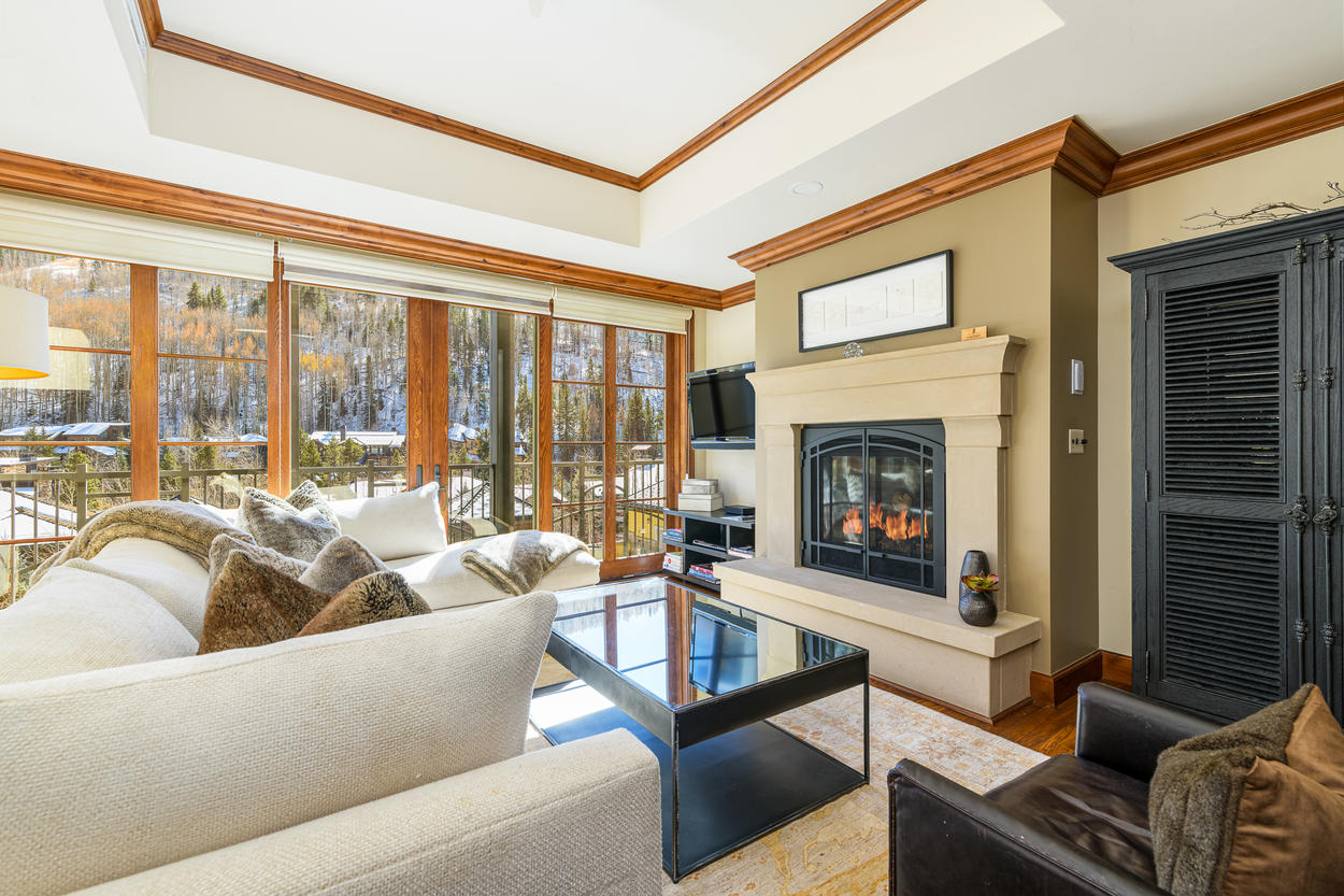 The living area has a large sectional couch that wraps around the gas fireplace.