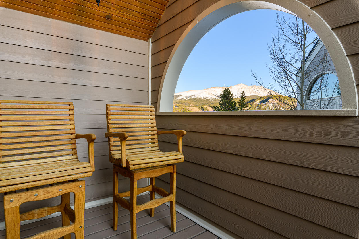 The covered deck on the fourth floor has mountain top views and comfy outdoor seating.
