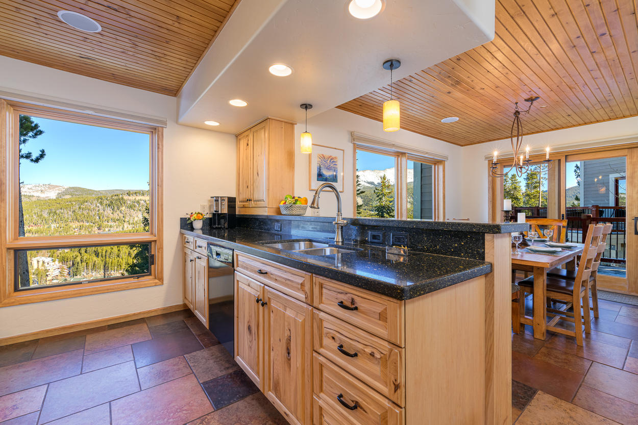 The kitchen shares the same incredible views as the living area, and features stainless steel appliances and polished stone countertops.