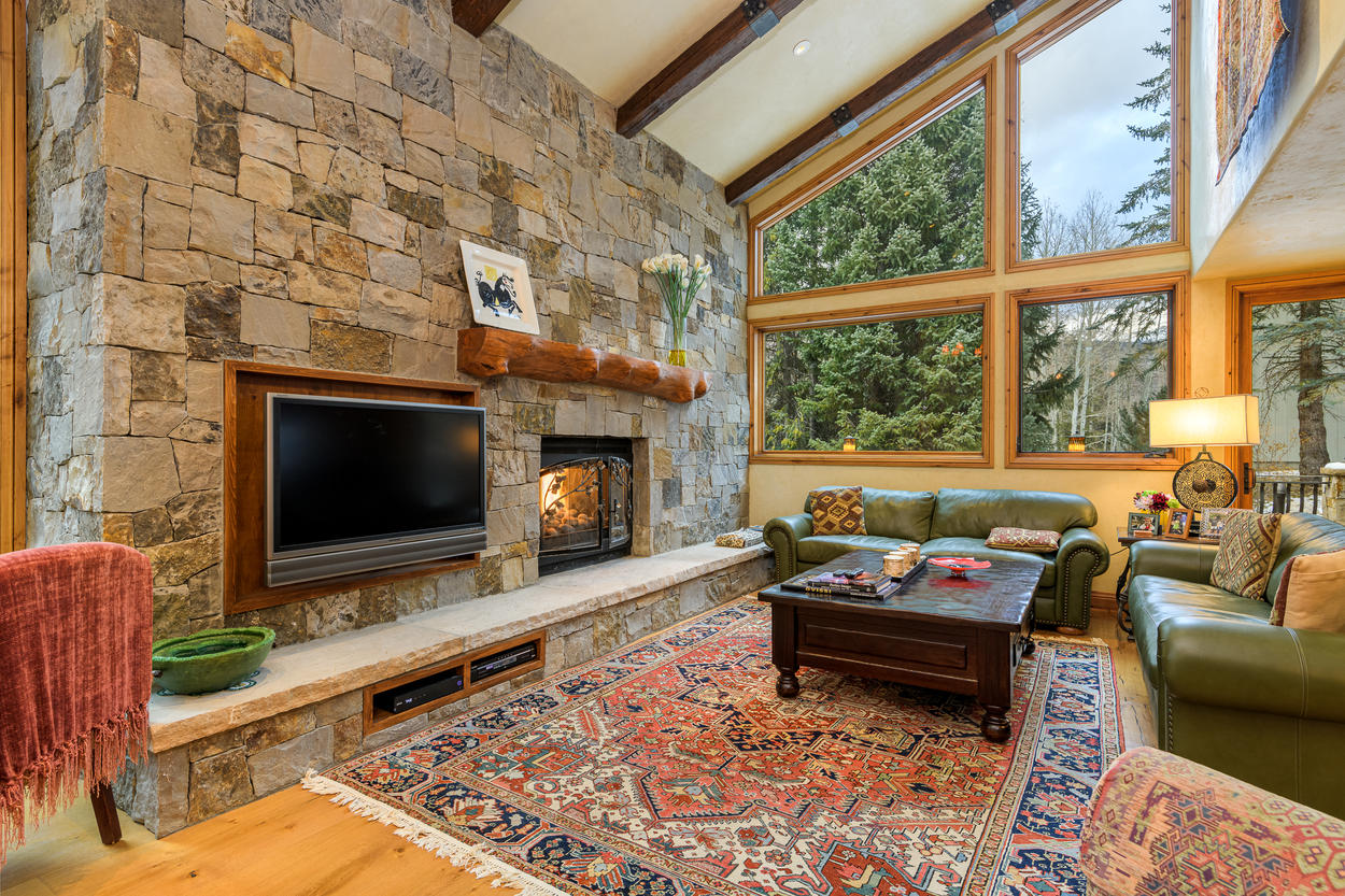 The far side of the living area features a cozy corner with a gas fireplace, two sofas, and a mounted TV.