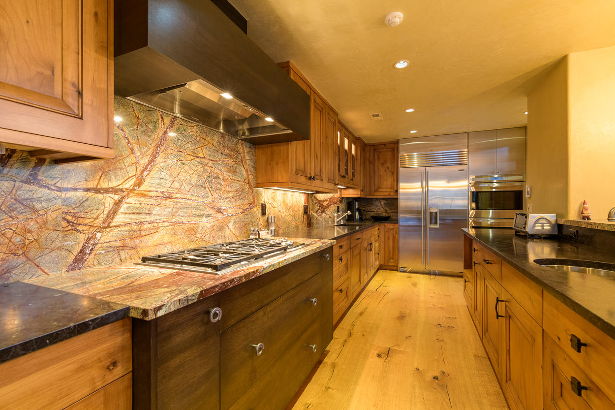 The custom kitchen features a 6-burner gas stove, hardwood floors, and rich wood cabinets.