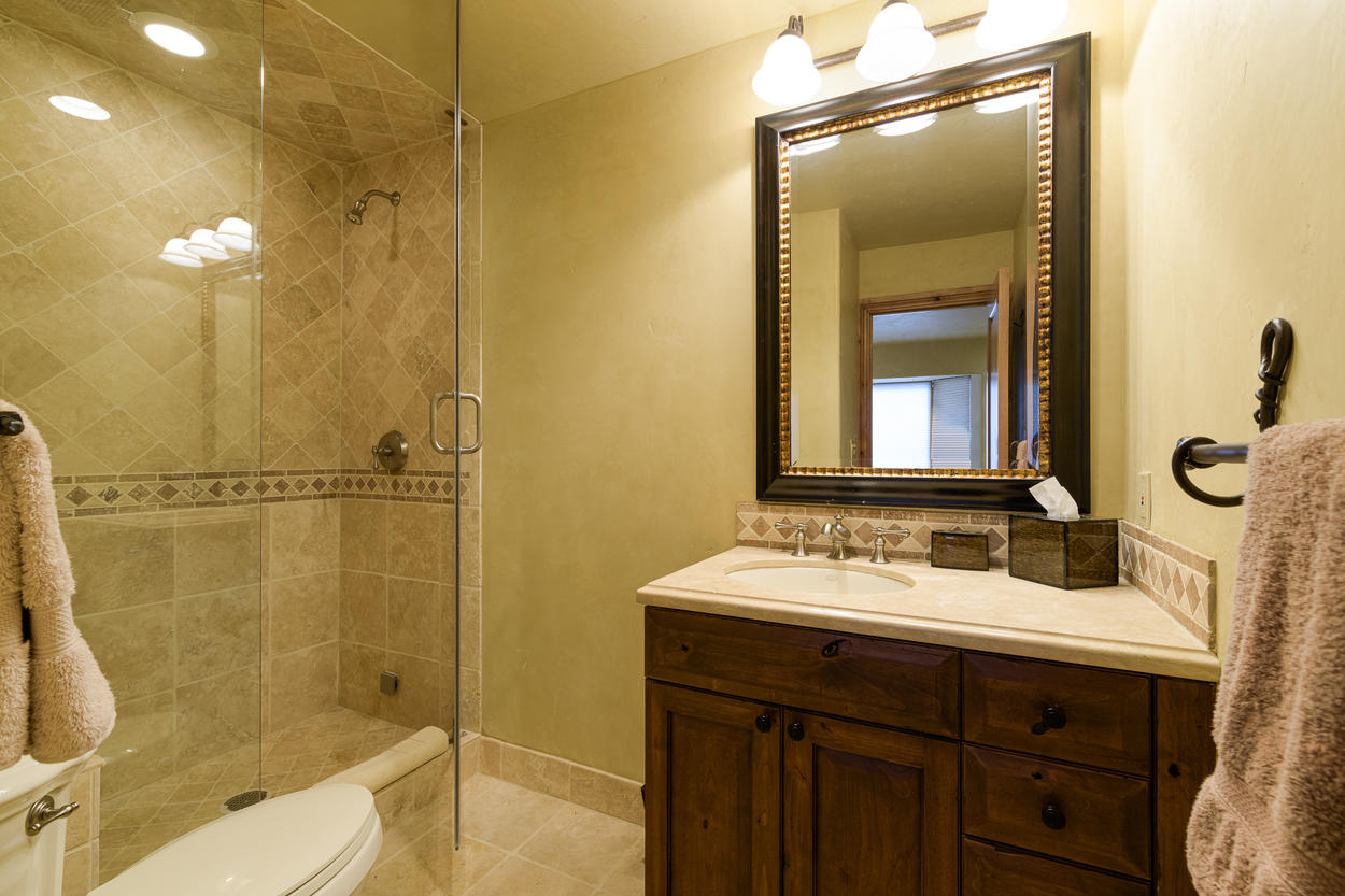 The 3rd floor twin room has an attached ensuite bathroom with a single vanity and a walk-in steam shower.